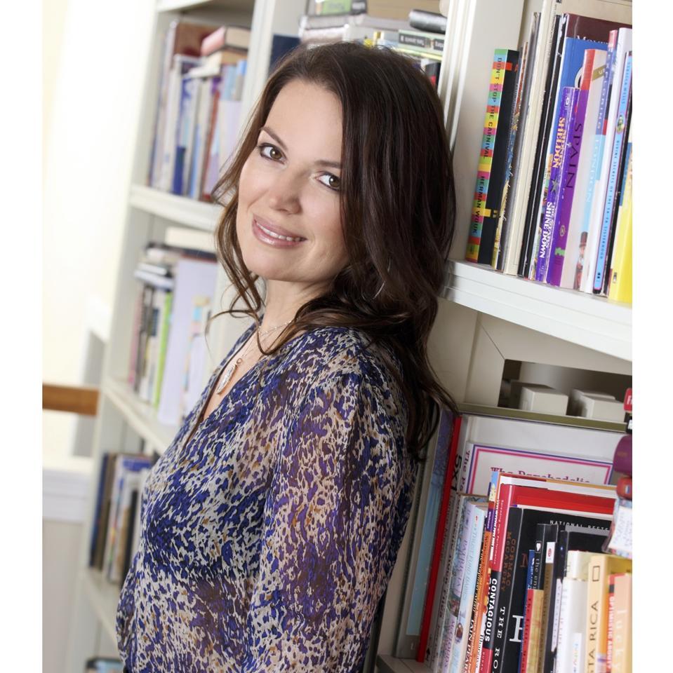 Julie Smolyansky stands against a bookshelf.