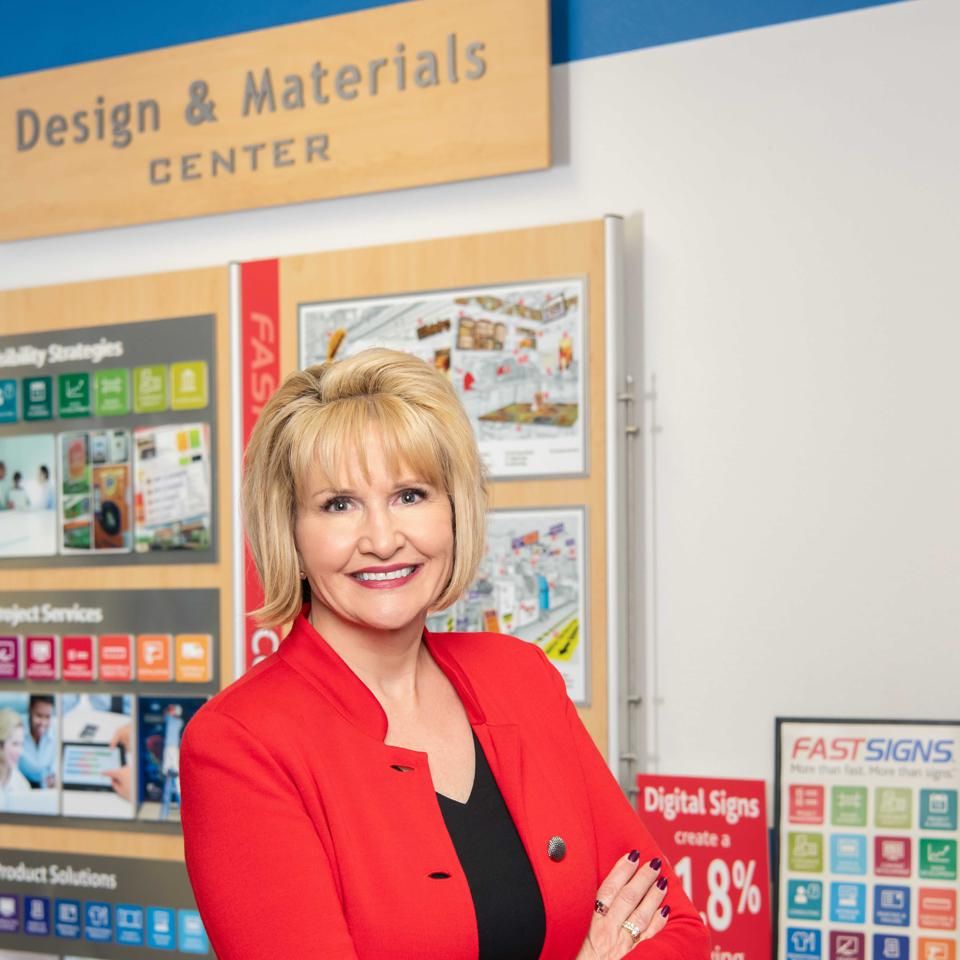 Monson poses in front a ″designs and materials″ board.