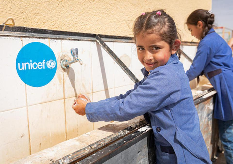 To prevent the spread of the novel coronavirus, Dareen, 6, washes her hands at a wash station set up by UNICEF in Jordan in 2020. ″I wash my hands so germs don't get on them,″ she says. ″Germs can make people sick or even kill them.″