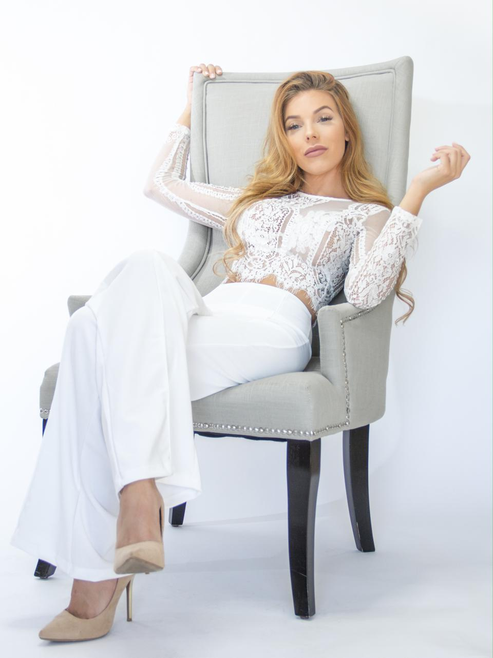 MelRose Michaels relaxes in a chair wearing a white lace top and white pants.
