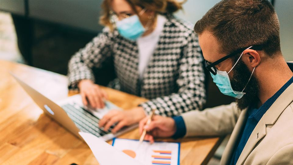 A man reading a spreadsheet and a woman at a laptop are both wearing surgical masks