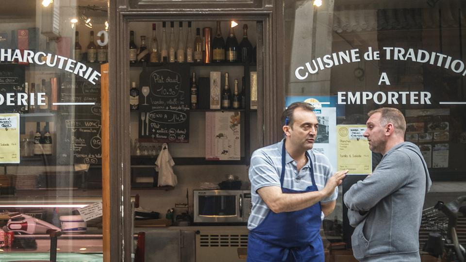 Two men talking in front of a cooking store in France