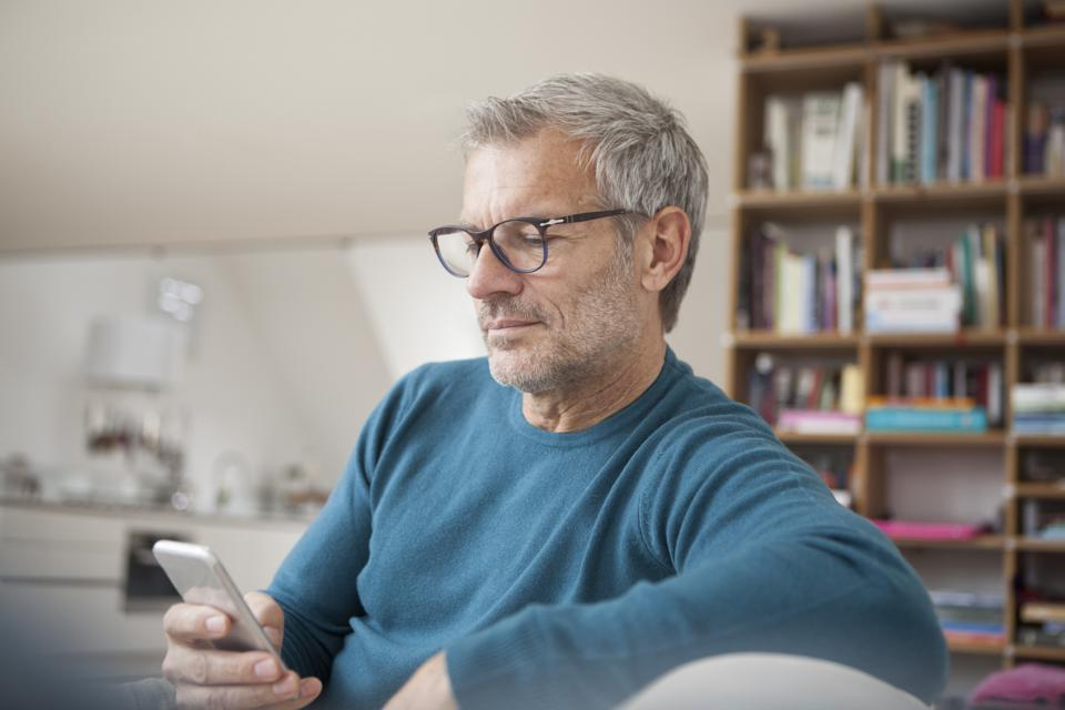 Mature man at home looking at cell phone