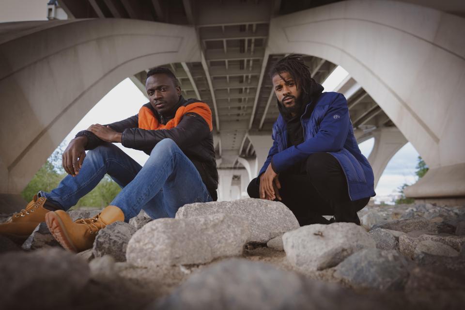 Two men sitting on rocks under a bridge