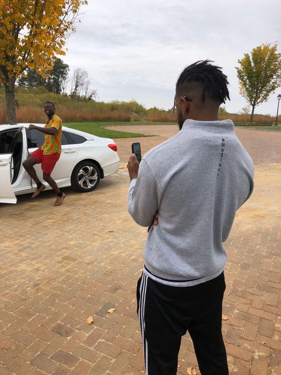 A man filming another man near a white car