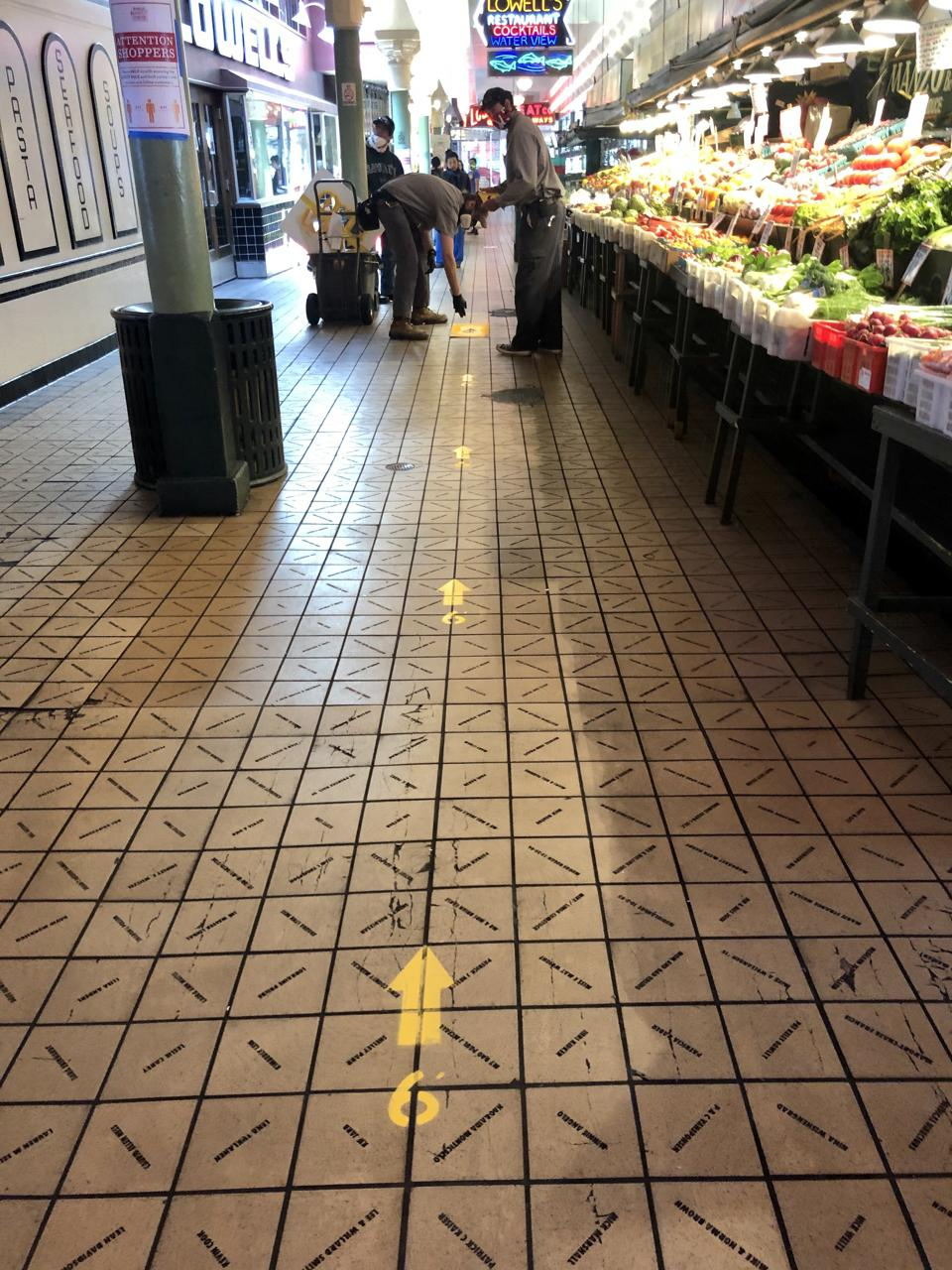 Pike Place Market in Seattle urges shoppers to keep social distance.