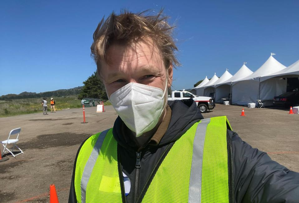 A man with a face mask takes a selfie in front of a row of temporary testing tents in a parking lot.