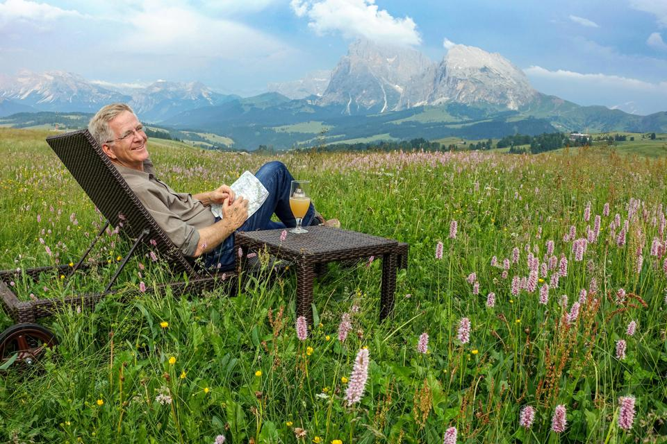Rick Steves relaxing with a drink near a Swiss mountain.