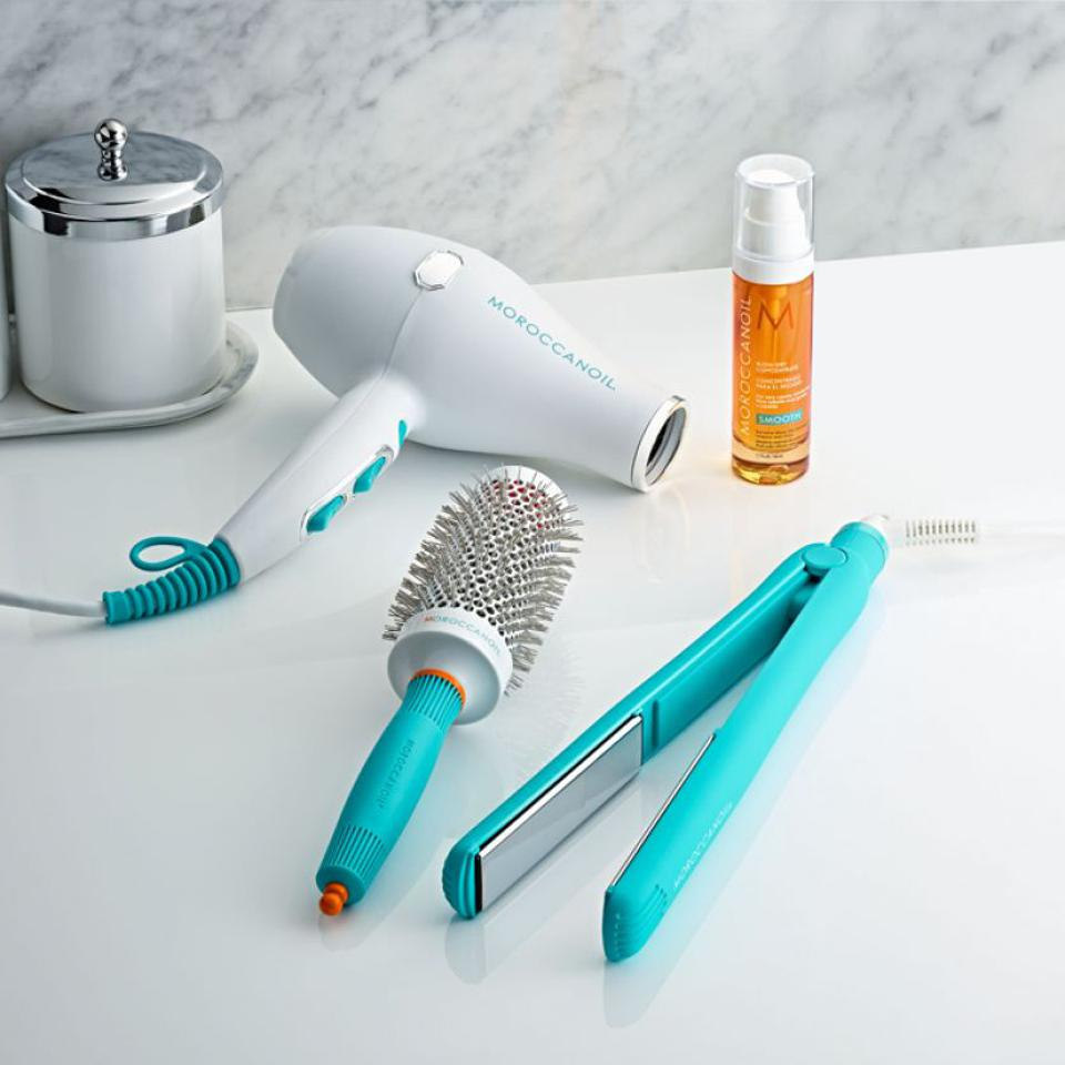 The Moroccanoil smart styling infrared hair dryer alongside other hair styling products.