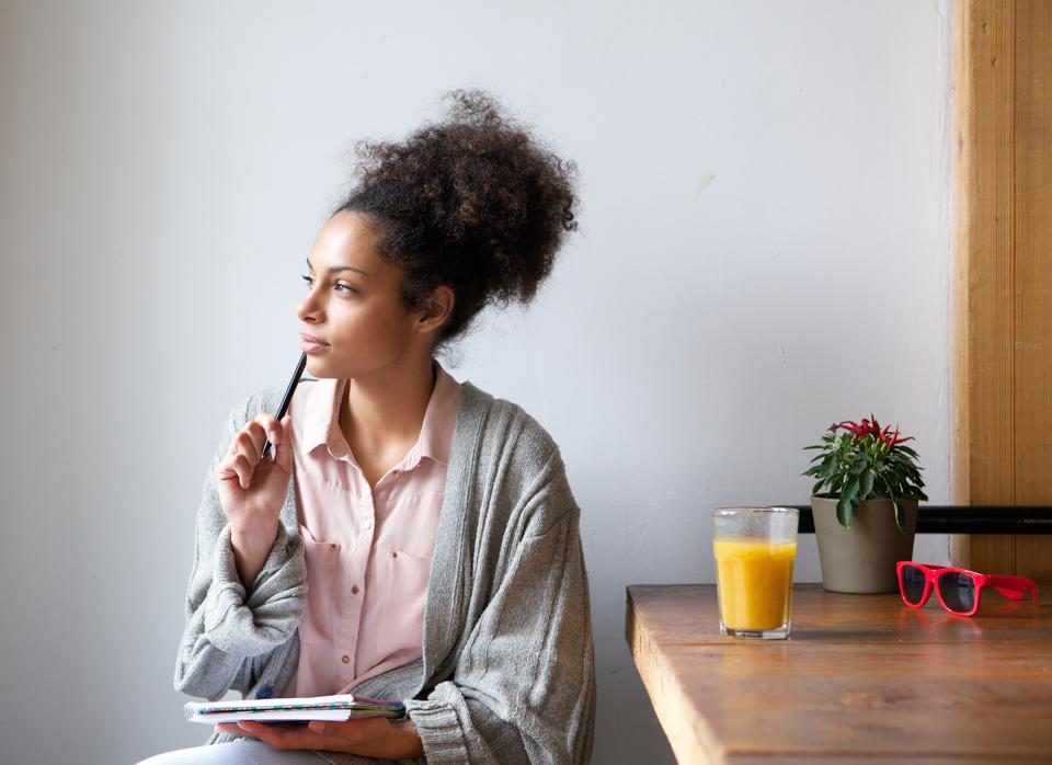 Young female sitting with pen and paper -- considering a career change?