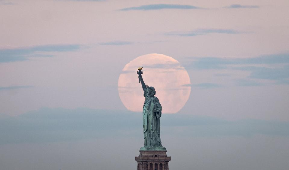 Full Flower Moon sets behind the Statue of Liberty in New York.