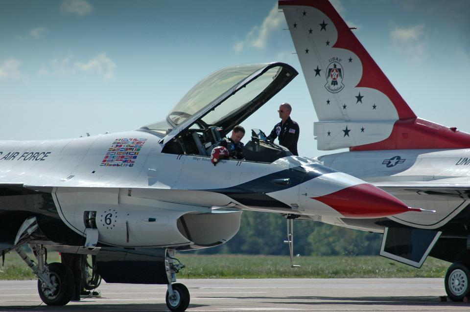 Two Thunderbirds pilots and their F-16s on the flight line.