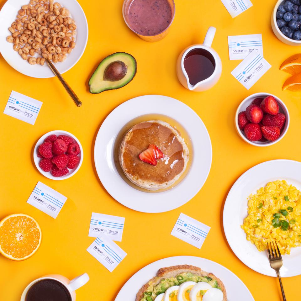 A BREAKFAST SPREAD FEATURING LOTS OF YUMMY THINGS, EGGS, PANCAKES, CEREAL, FRUIT, CALIPER