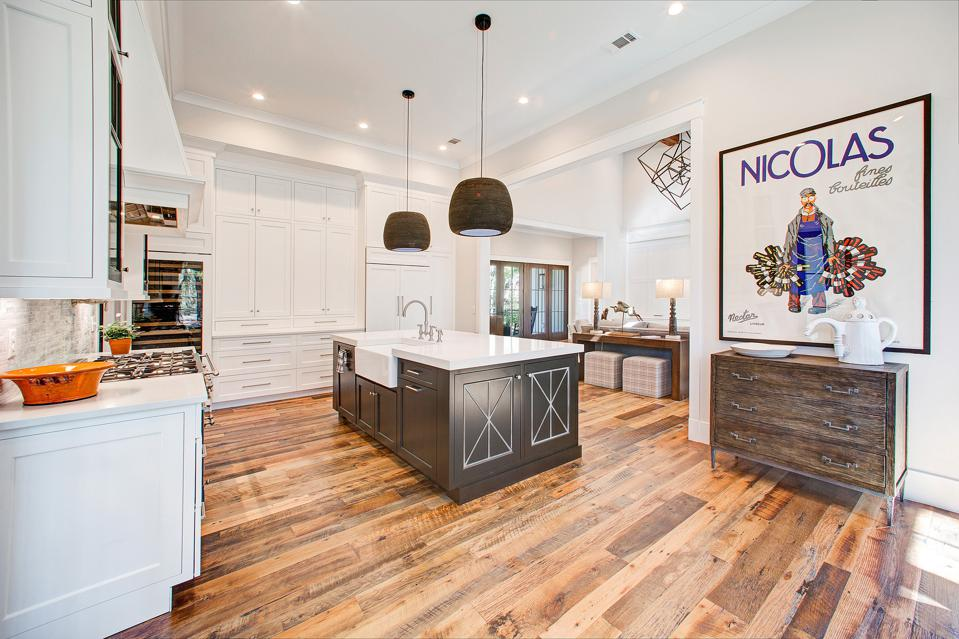 Adjacent to the great room there's an eat-in gourmet kitchen with Caesarstone counters, custom cabinets, Sub-Zero refrigerator, wine cooler, as well as a back kitchen with additional storage.
