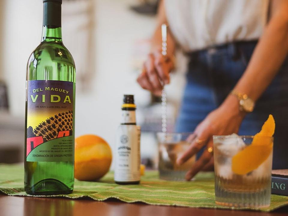 A bottle of mezcal and a girl mixing a cocktail