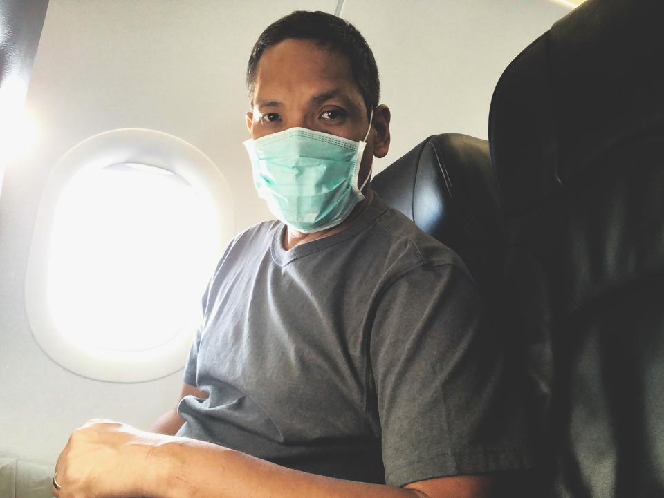 Portrait Of Man Wearing Mask Sitting In Airplane