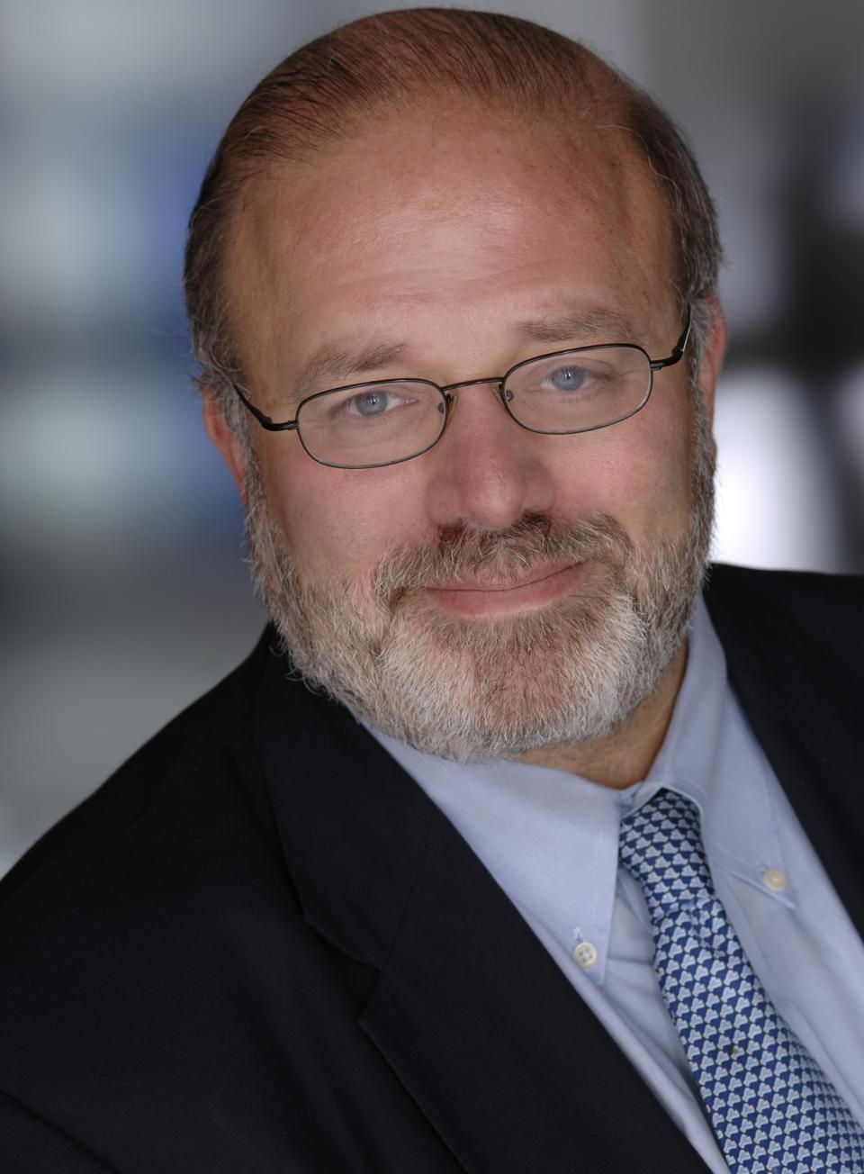 A man with a beard in glasses, a dark jacket and a shirt and blue tie.