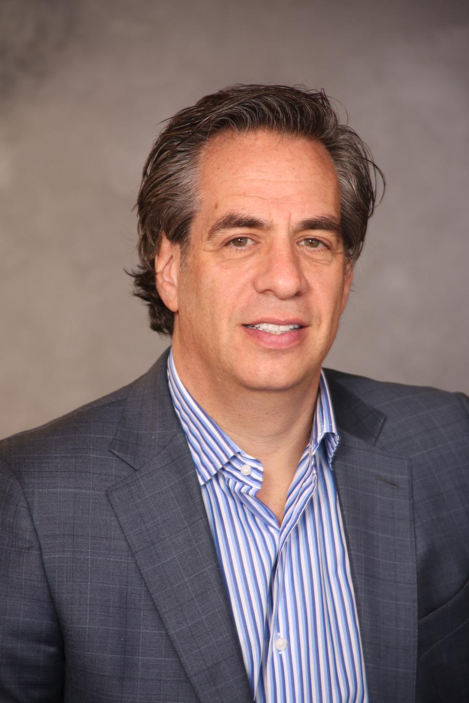 A man in a gray sport jacket and blue and white striped shirt.