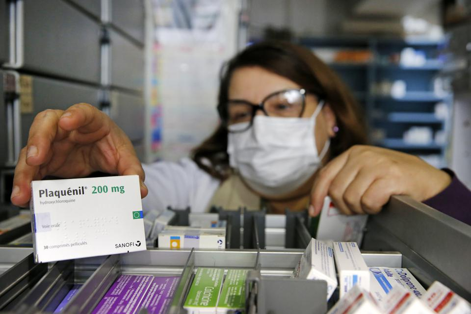 A pharmacy employee shows a box of Plaquenil (Hydroxychloroquine) on March 27, 2020 in Paris, France.