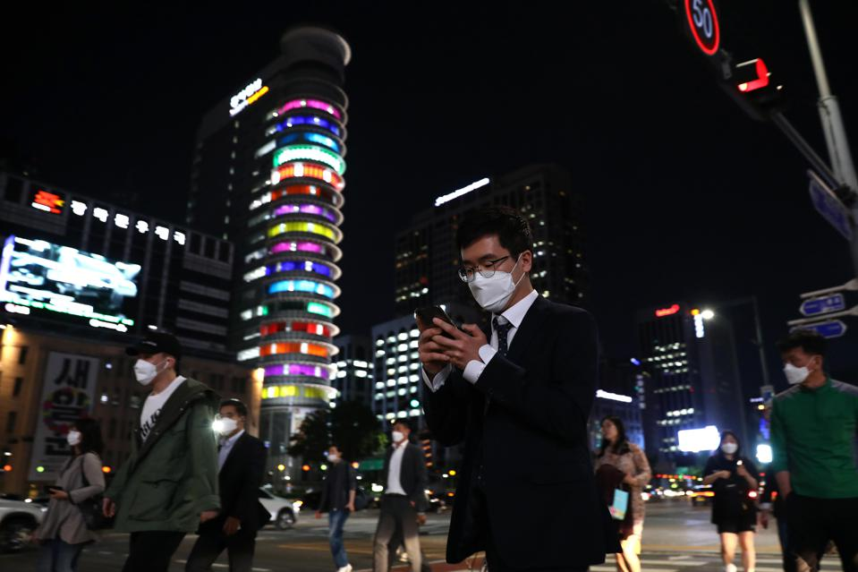 People walk along the street in face masks in Seoul.
