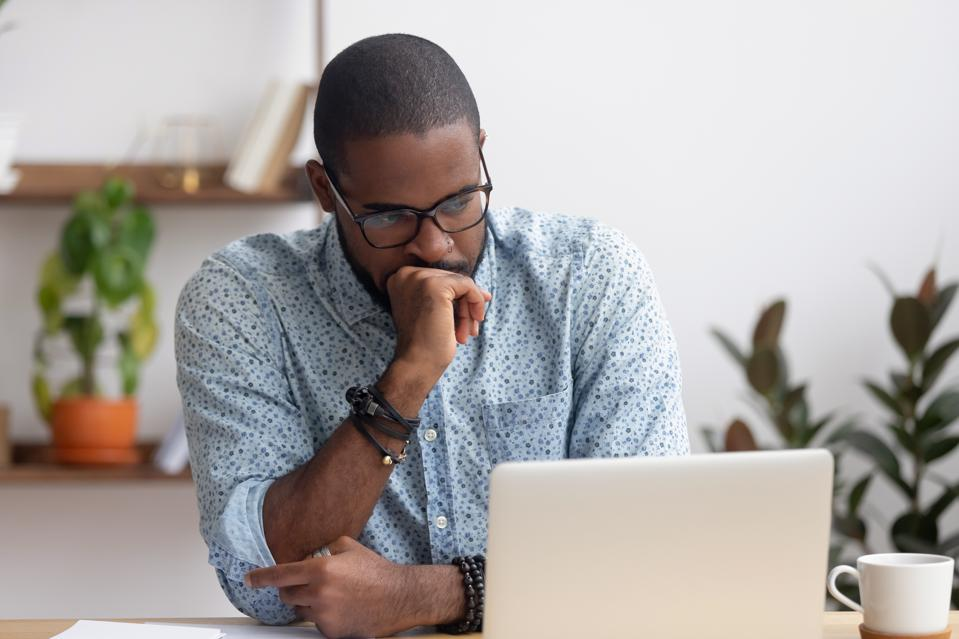 Head shot serious puzzled African American businessman looking at laptop