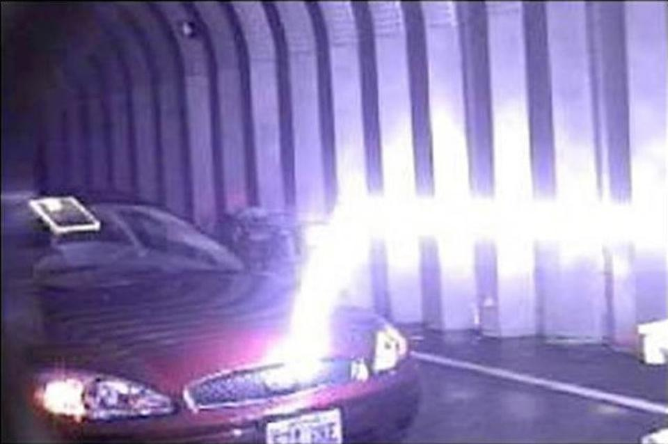 A bolt of artificial lightning striking a car in a laboratory