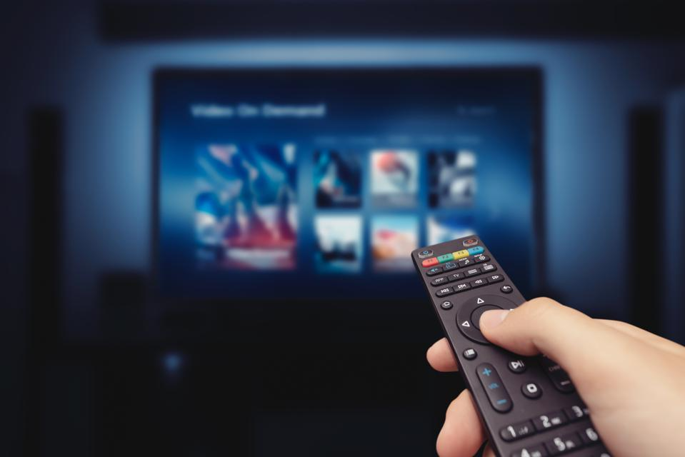 VOD service screen with remote control in hand