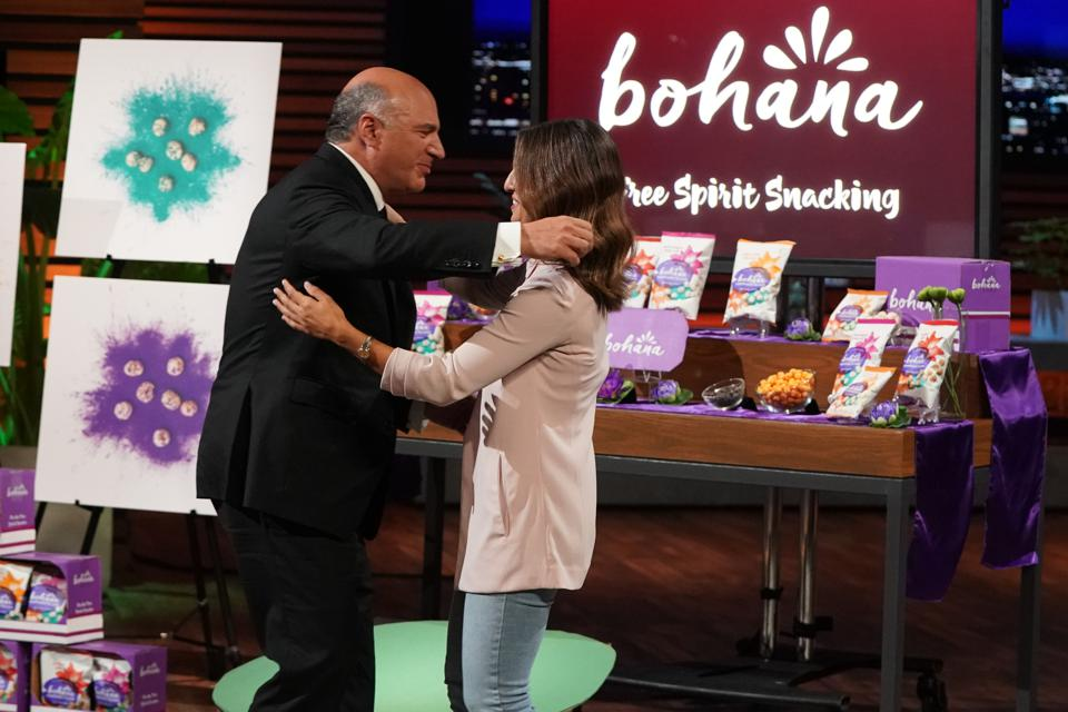 Shark Kevin O'Leary hugs Nadine Habayeh to celebrate the dealmaking moment.