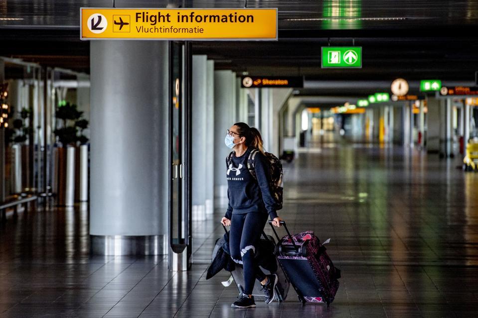 A traveller wears a face mask
