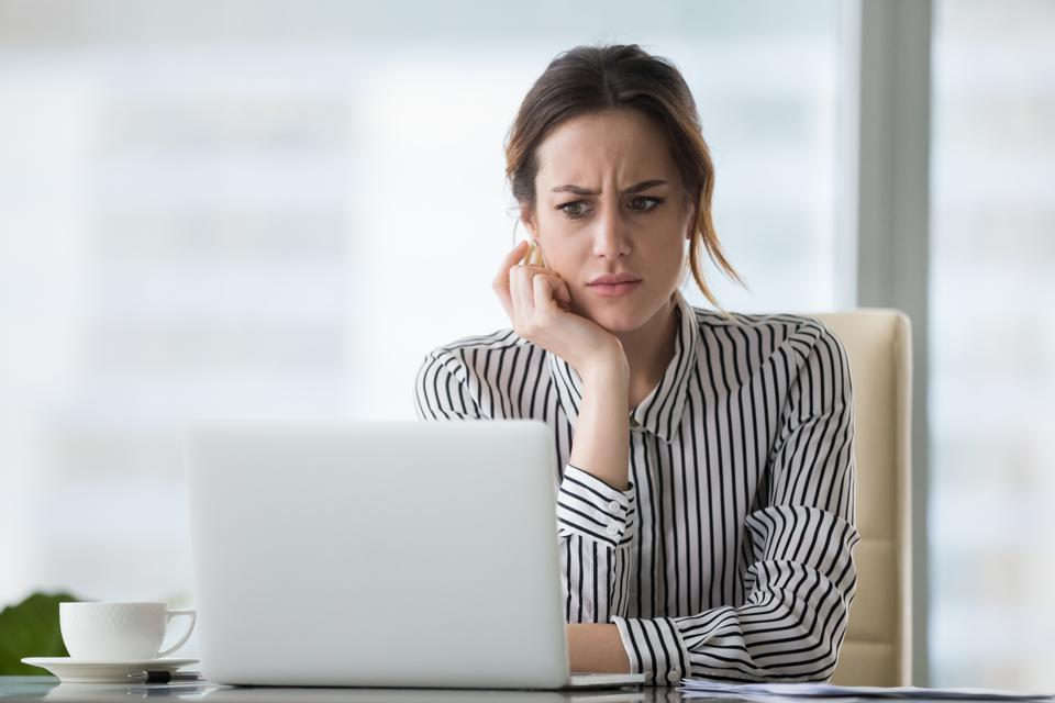 Confused businesswoman annoyed by online problem looking at laptop