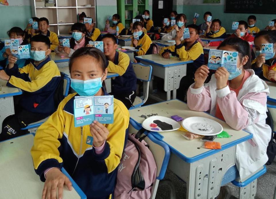 Students at a school in Datong County, Qinghai Province, China, hold up health education leaflets developed by UNICEF to support their safe return to school.