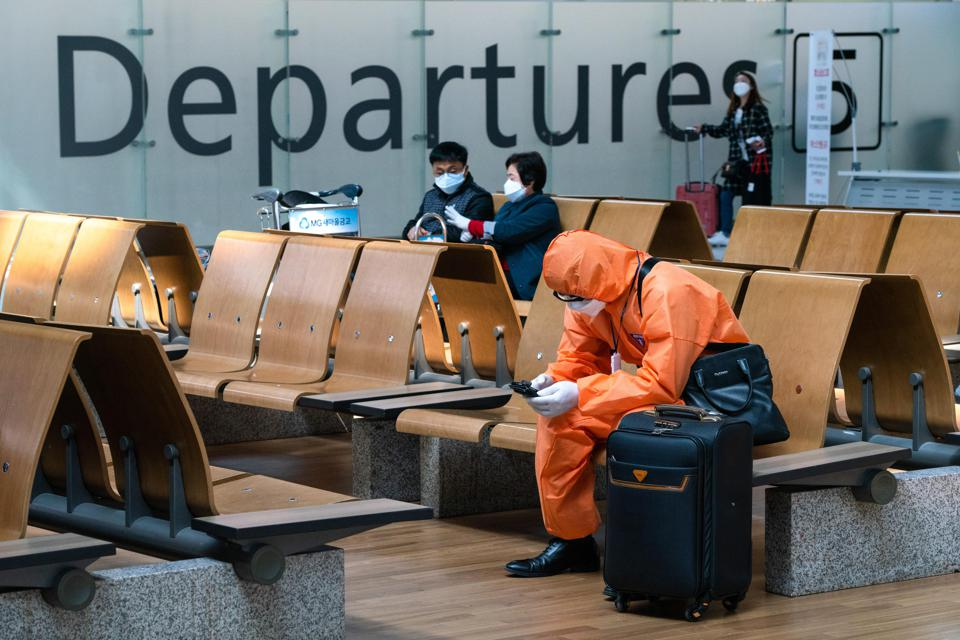 A man wearing a protective suit sits at the departure hall of Incheon Airport.
