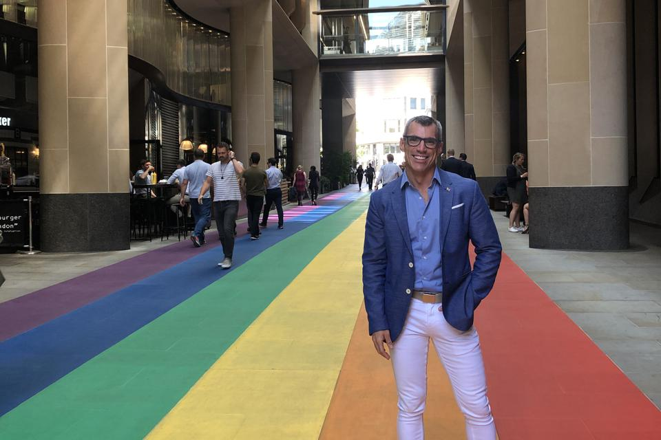 Borok standing on rainbow flooring during Pride month in London