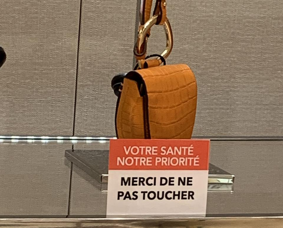 An image of a brown suede Chloe handbag next to a sign saying please do no touch in French