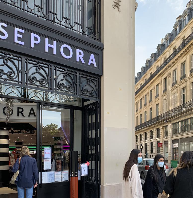 A street scene depicting shoppers in masks and exterior of Sephora on Boulevard Haussman in Paris