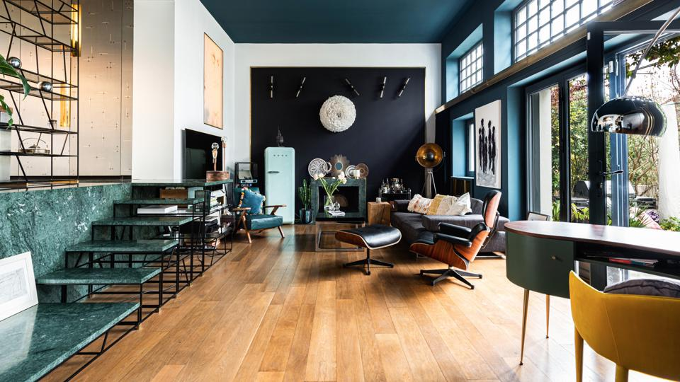 A large living room with high ceilings and teal walls lit by glazed doors