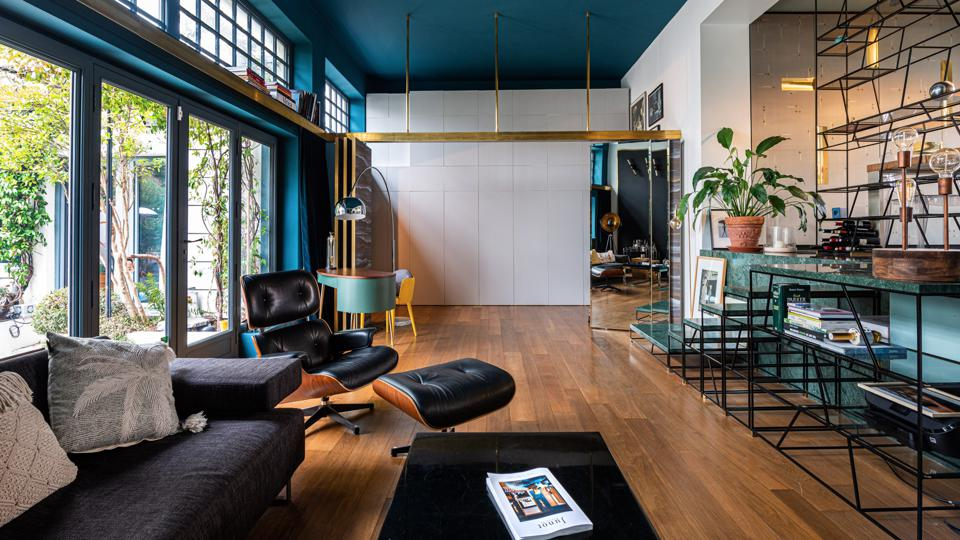 The living room has polished timber flooring and a concertina glass and brass screen