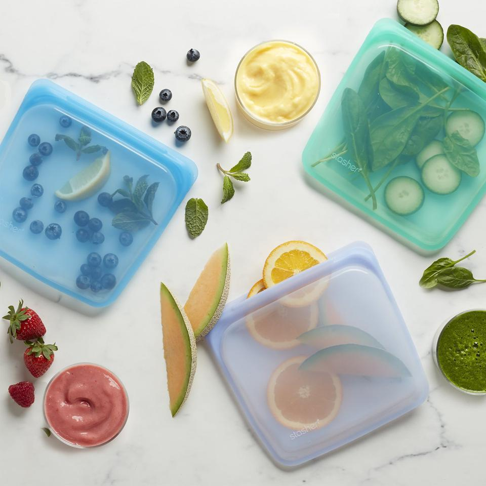 Reusable silicone food bags by stasher shown holding cut fruit