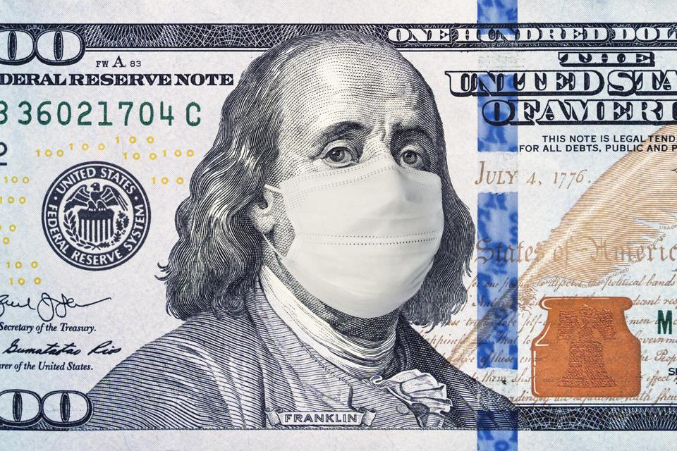 American President with a face mask against coronavirus infection on a 100 dollar banknote.