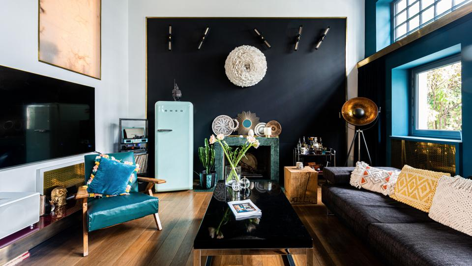 A dark feature wall adds drama to the room