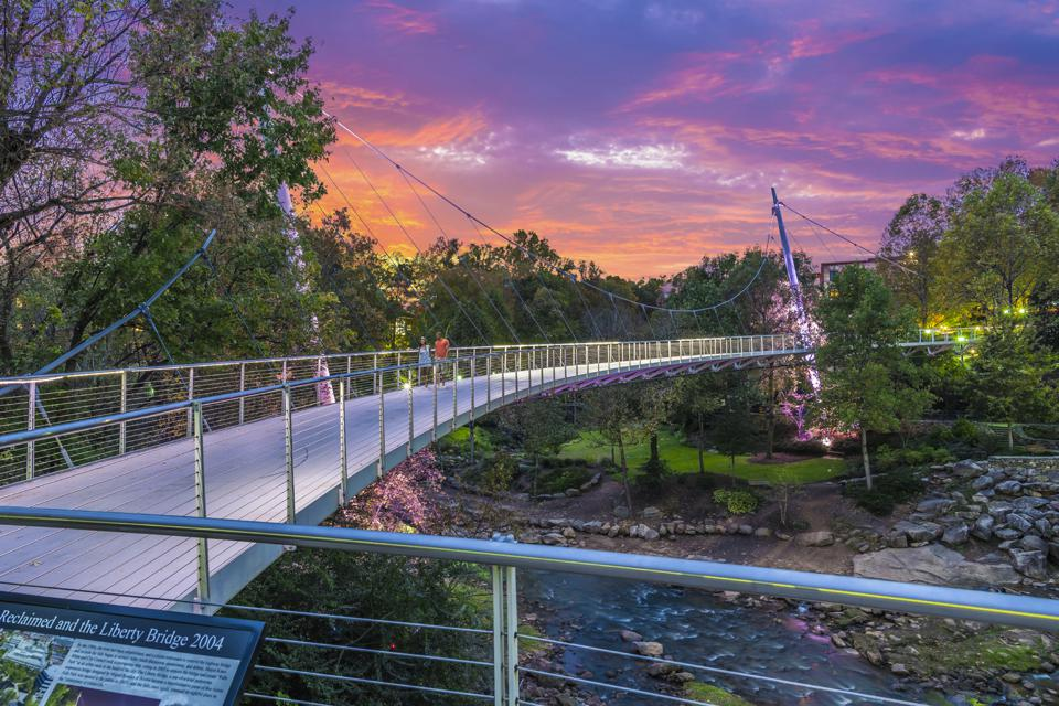People strolling leisurely over an isolated bridge in Greenville.