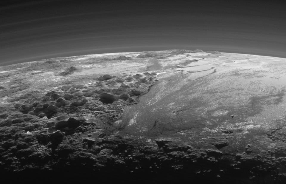 Just 15 minutes after its closest approach to Pluto on July 14, 2015, NASA's New Horizons spacecraft looked back toward the sun and captured this near-sunset view of the rugged, icy mountains and flat ice plains extending to Pluto's horizon. The smooth expanse of the informally named Sputnik Planum (right) is flanked to the west (left) by rugged mountains up to 11,000 feet (3,500 meters) high, including the informally named Norgay Montes in the foreground and Hillary Montes on the skyline. The backlighting highlights more than a dozen layers of haze in Pluto's tenuous but distended atmosphere. The image was taken from a distance of 11,000 miles (18,000 kilometers) to Pluto; the scene is 230 miles (380 kilometers) across.