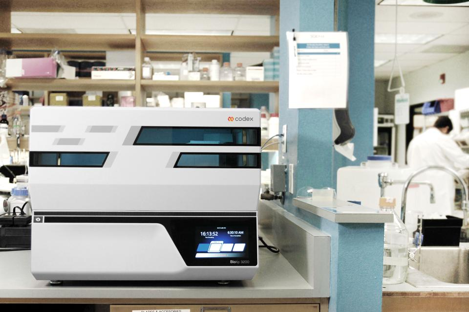 A laboratory machine, the size of a large printer, sits on a lab bench.
