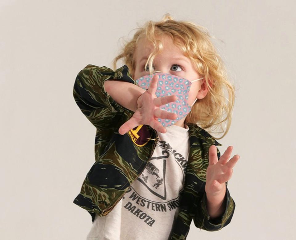 A child in a Sanctuary Clothing printed mask, playing