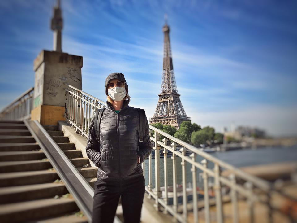 The author stands in a mask in front of the Eiffel Tower.