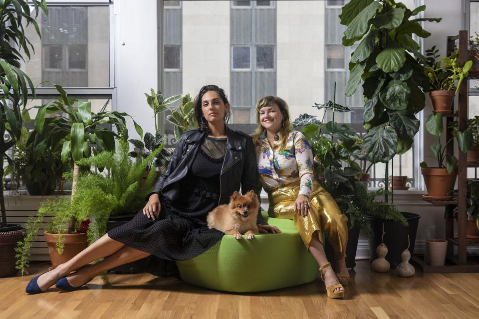 Gallery owners posing with their dog