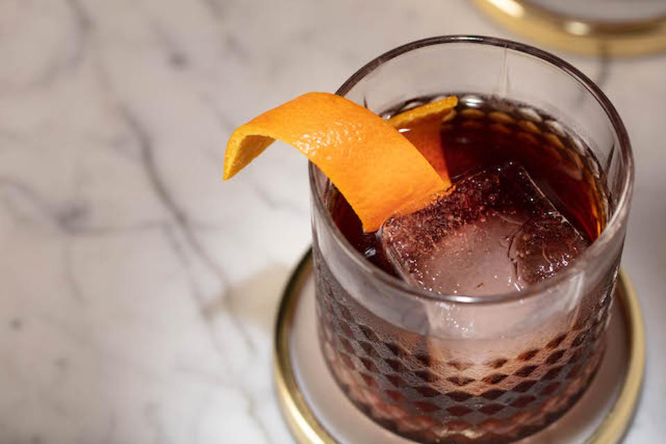 a glass with an ice cube and vermouth