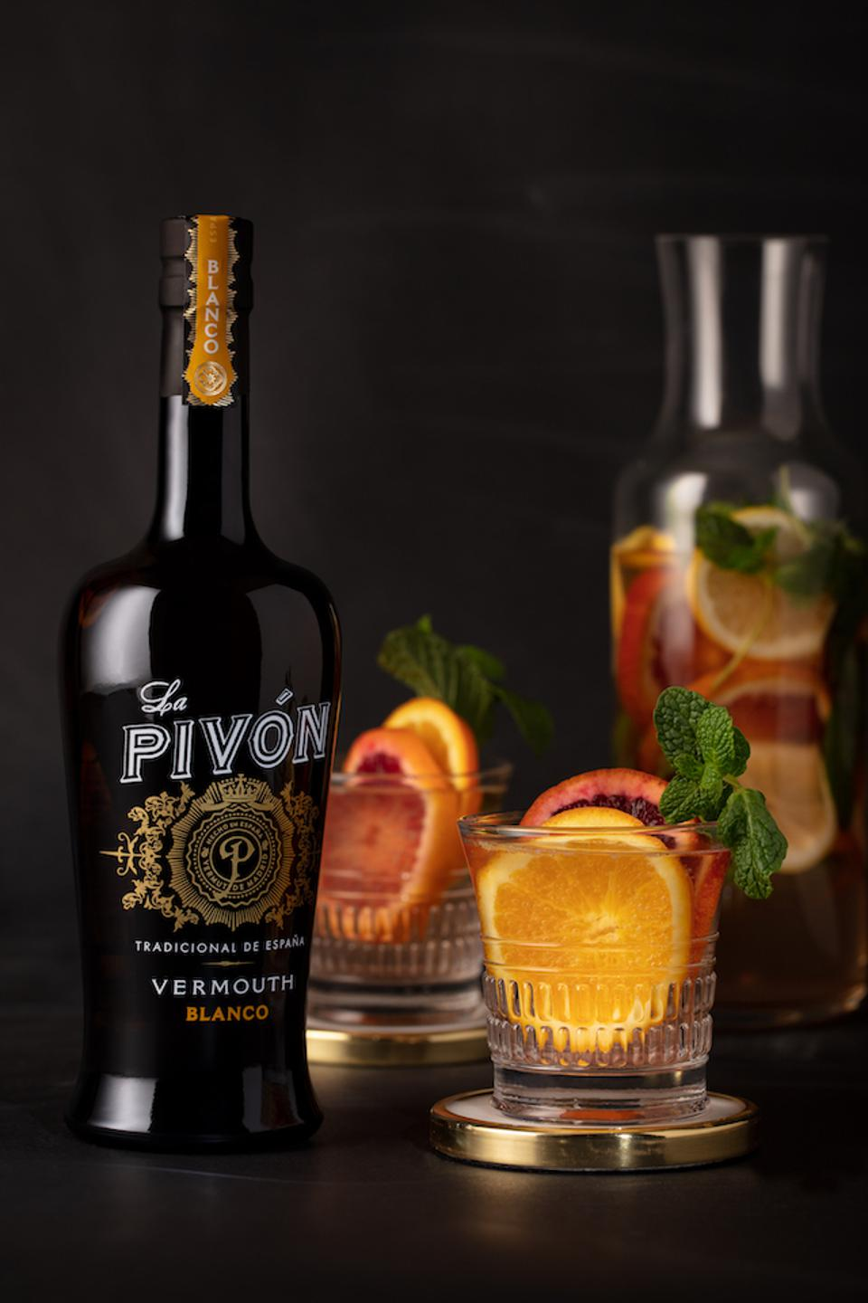 a bottle of la pivon white vermouth and a short glass with some orange slices in it.