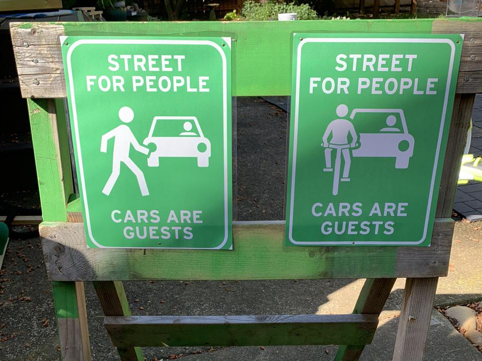Painted signs reading ″Street for People / Cars are Guests″ on sawhorse