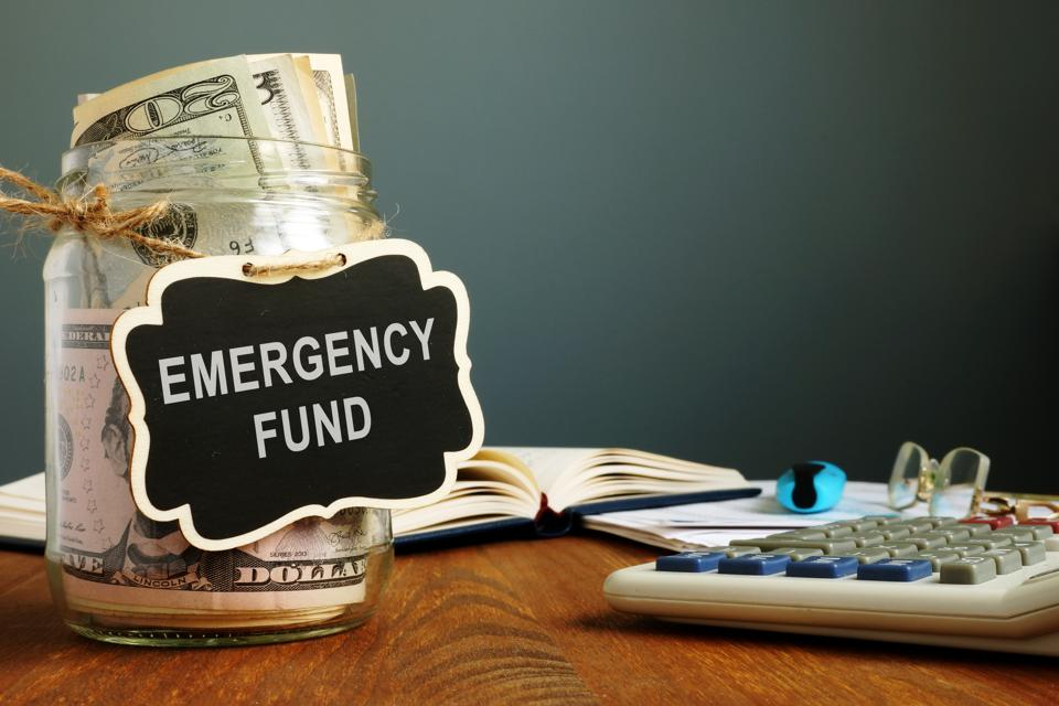Emergency fund savings written on the jar with money.